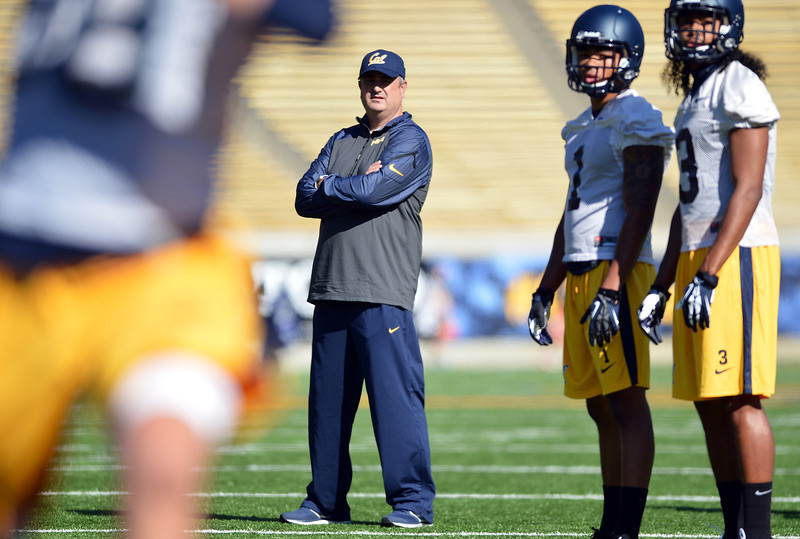 Sonny, Treggs, and Mo Harris go over the Bear Raid offense inside Memorial Stadium (Kristopher Skinner/BayArea News Group)